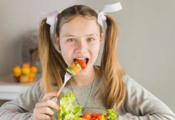 portrait-girl-eating-fresh-vegetable-salad-with-fork_23-2147873745