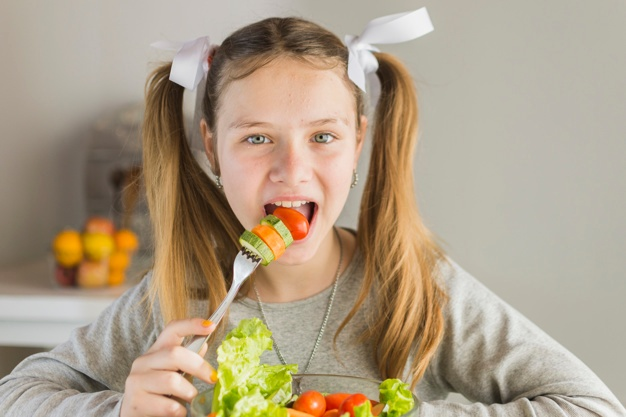 portrait-girl-eating-fresh-vegetable-salad-with-fork_23-2147873745